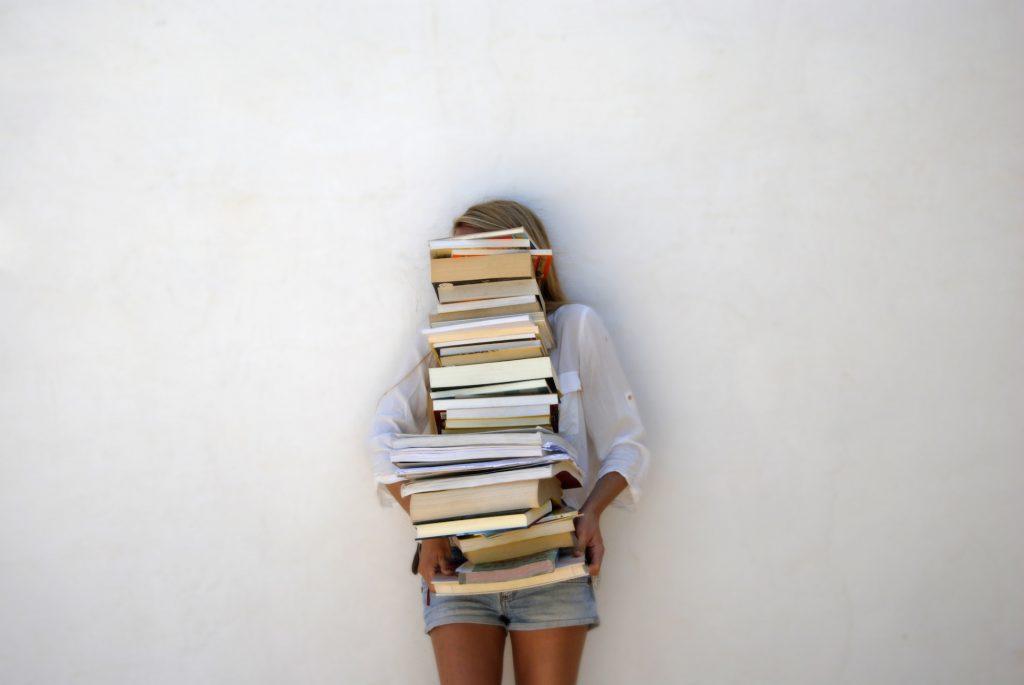 Meisje met stapel boeken