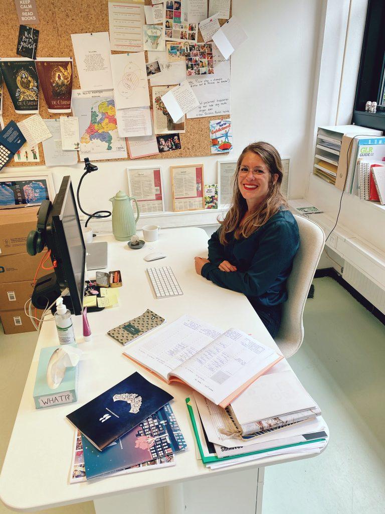 Myrthe achter haar bureau op kantoor